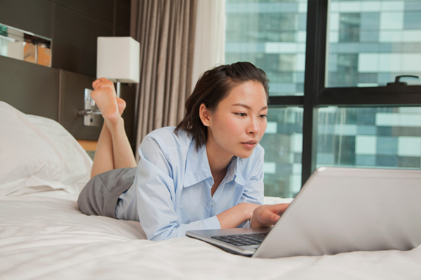 Woman working on laptop in hotel room | Sheknows.com