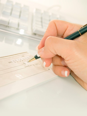 Woman Writing Check in front of Keyboard