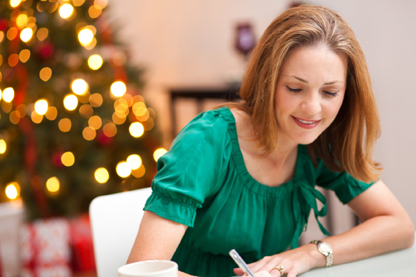 Woman writing note to husband on Christmas