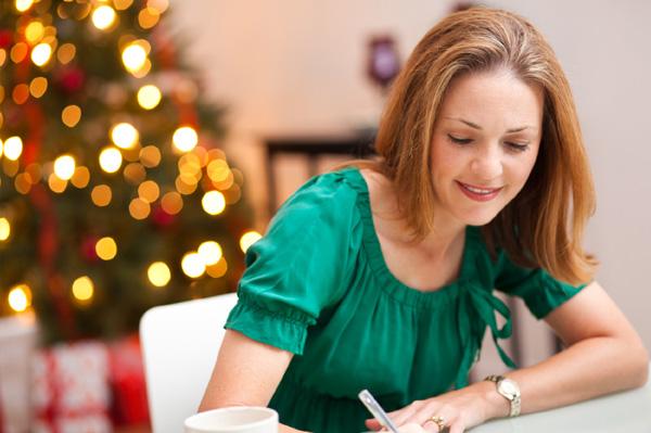 Woman writing note to husband on Christmas