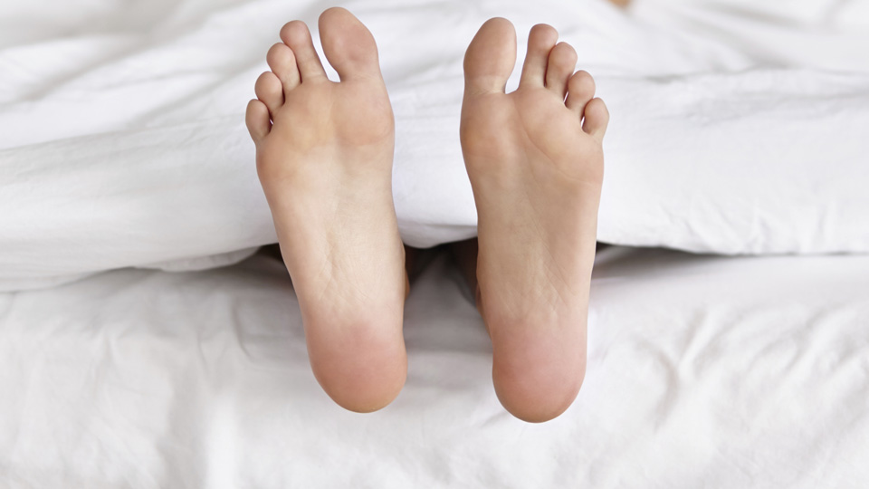 Womans feet sticking out of bed