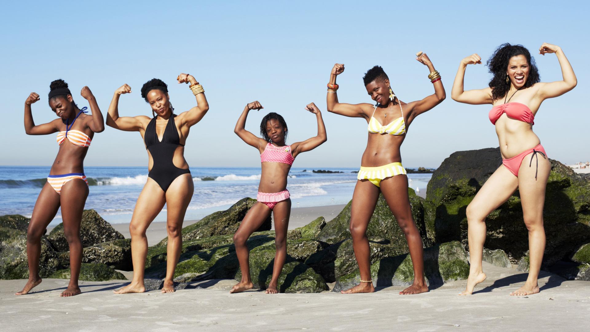 Women striking power pose on beach | Sheknows.com