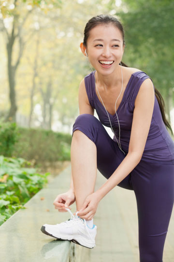 young woman tieing shoe while jogging