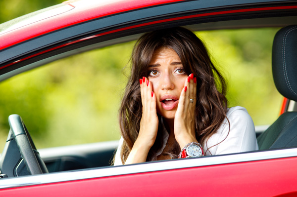 Worried woman after she hears a loud noise from her car