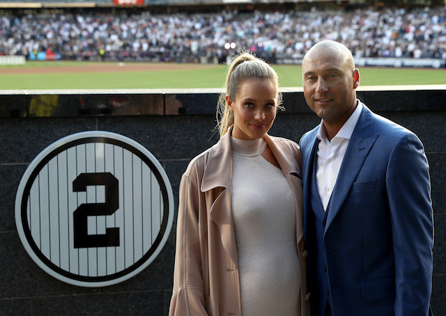 Hannah & Derek Jeter pose next to his number in Monument Park at Yankee Stadium