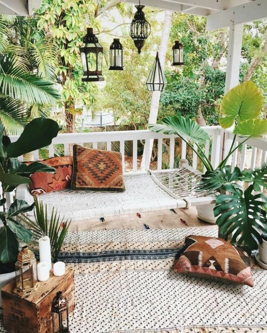 Porch with plants and pillows on the floor