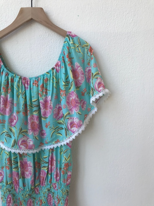 Floral romper hanging on white wall