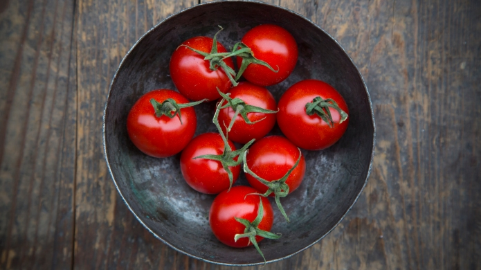 Bowl with cherry tomatoes on wooden