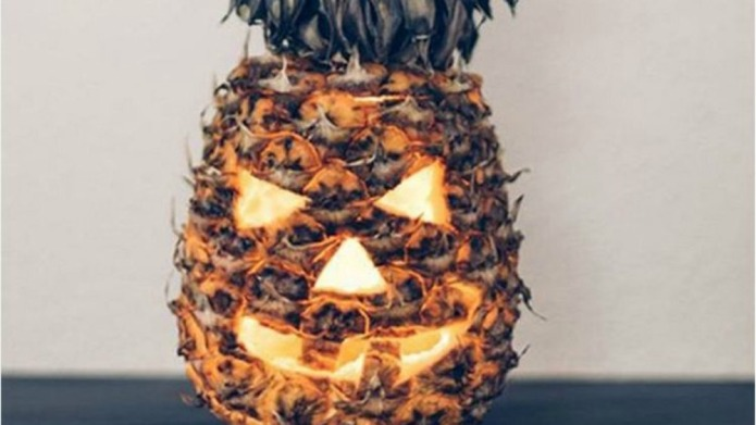 People are carving pineapples into jack-o'-lanterns,