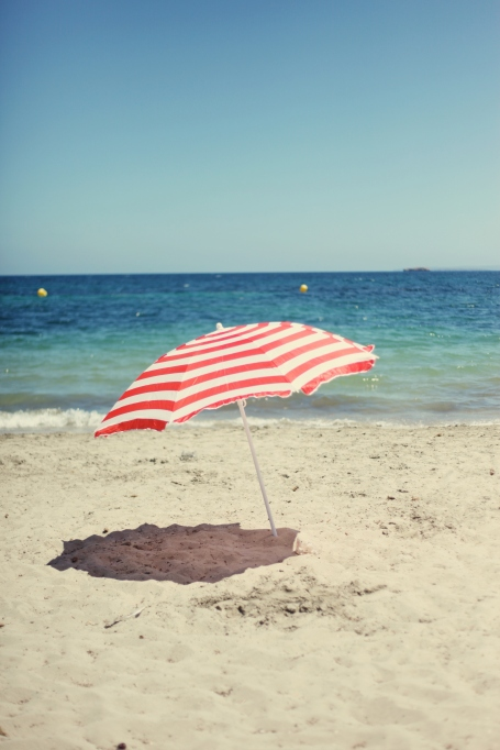 Red and white striped umbrella on the beach.