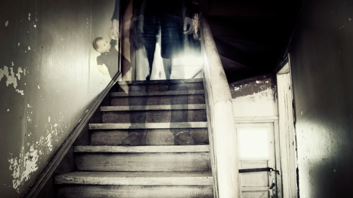 Ghostly figure standing on stairs inside