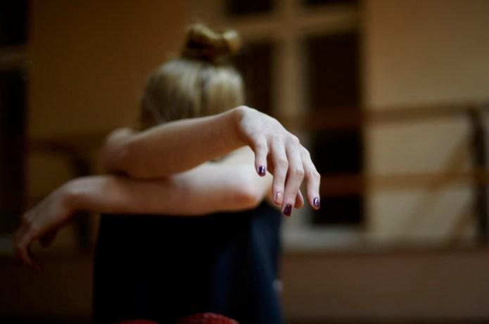 Fatigued Caucasian dancer sitting on studio