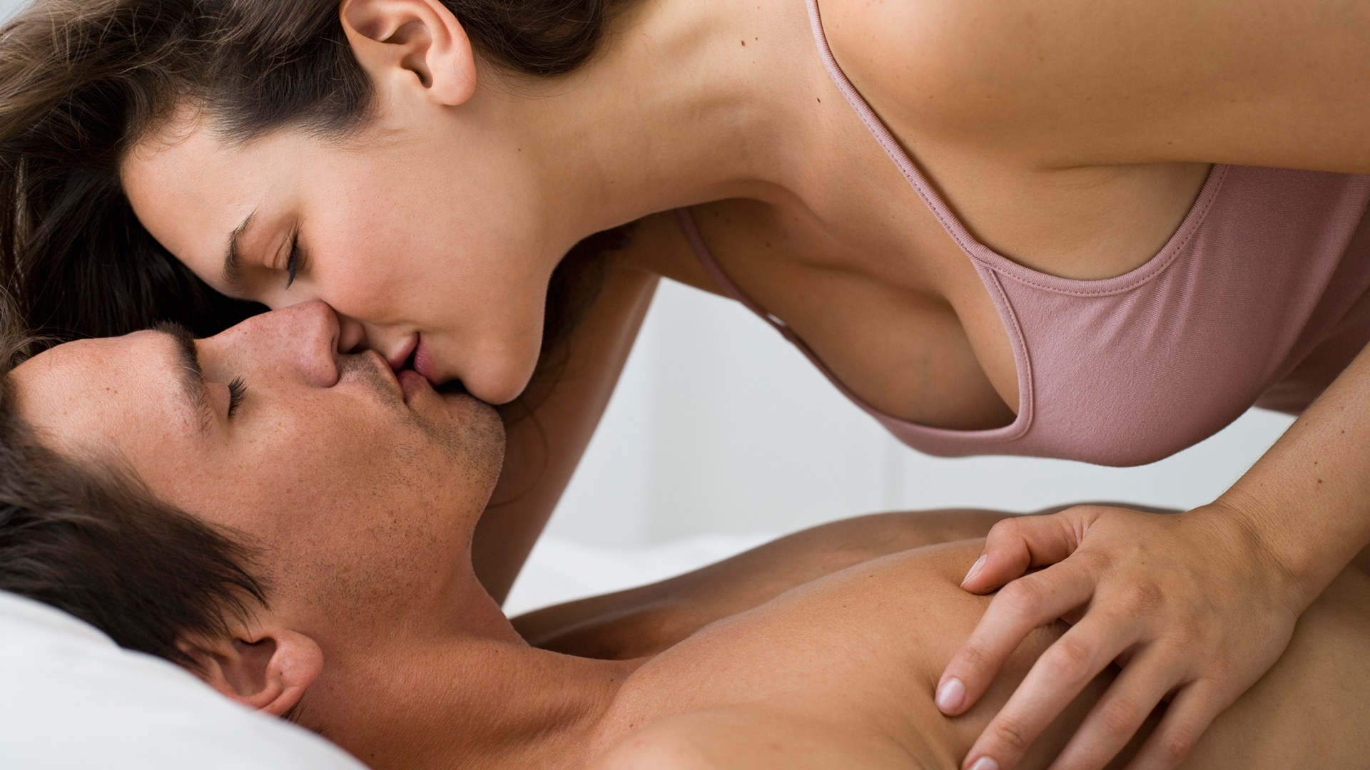 Young couple kissing in bed | Sheknows.ca