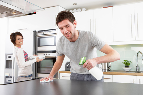 Young husband helping wife clean kitchen