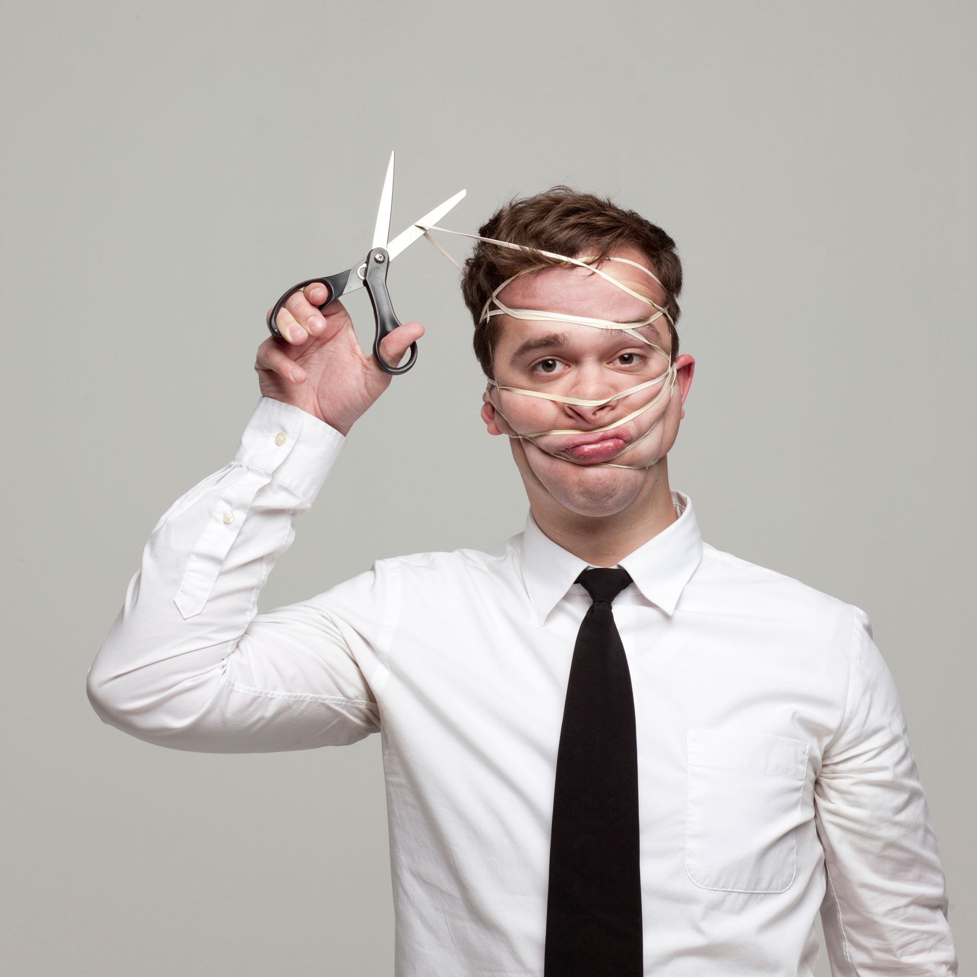 young man with tied face trying to cut rope