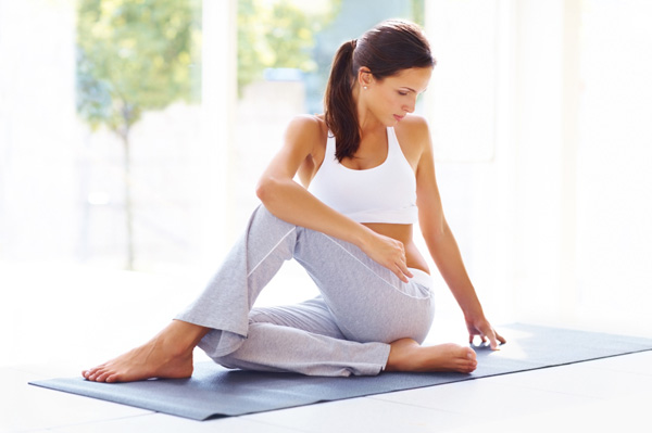Young stylish woman on yoga mat