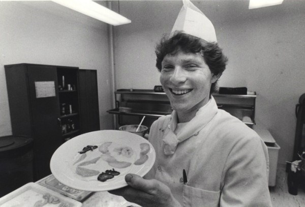 Young Bobby Flay showing off a plate of food.