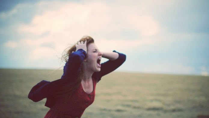 Young woman screaming in windy, cloudy