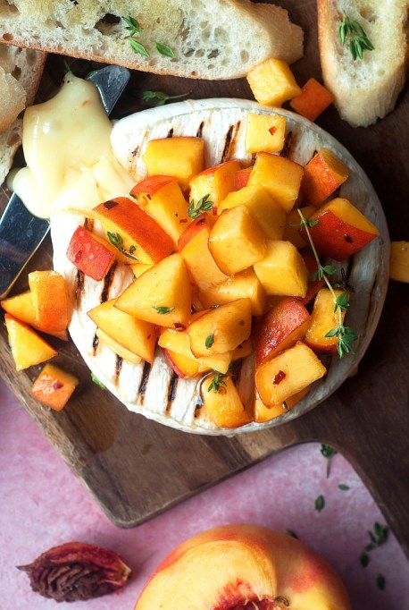 Summer Peach Recipes: Grilled brie topped with peaches is an effortless summer appetizer.