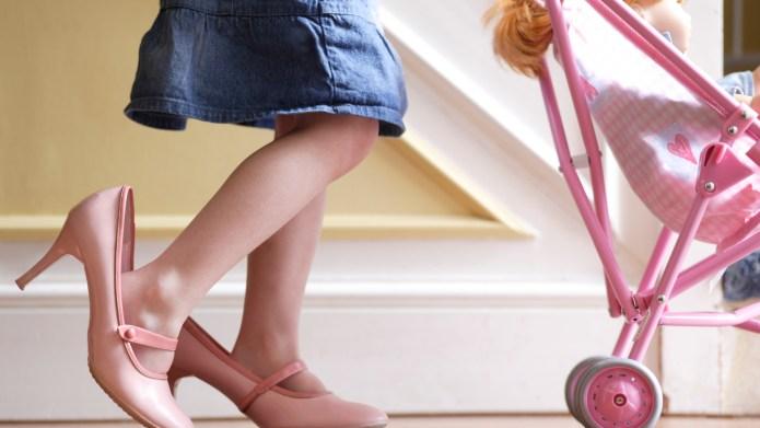 Girl (3-5) wearing adult shoes, pushing