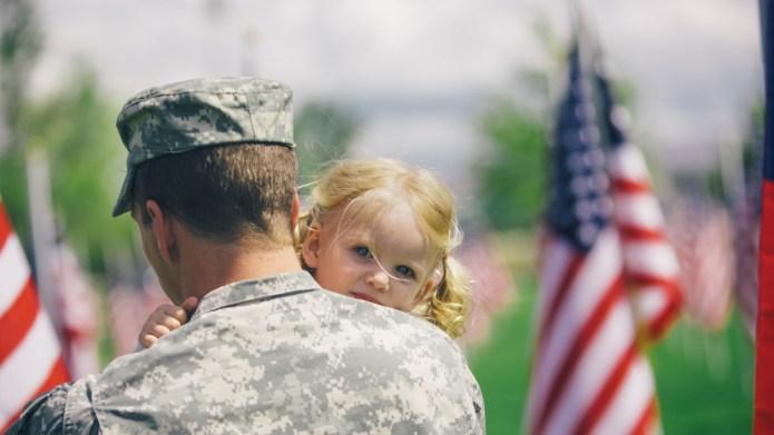 American soldier hugging his toddler daughter