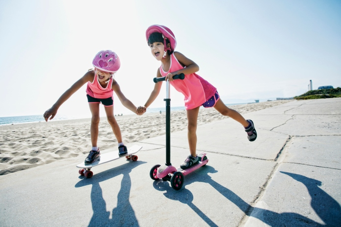 Girls riding skateboard and scooter at