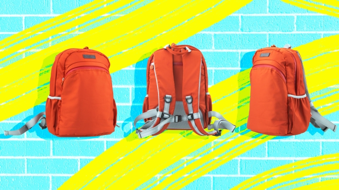 school backpacks against neon brick wall