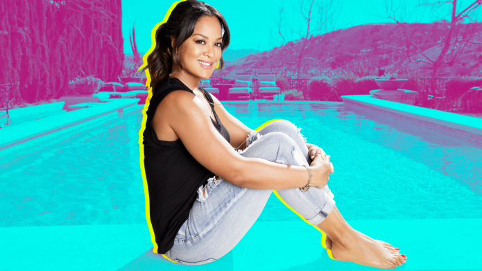 Laila Ali sitting down holding her