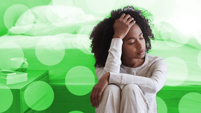 Black woman holding forehead against green
