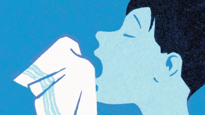 Woman mid-sneeze using a handkerchief