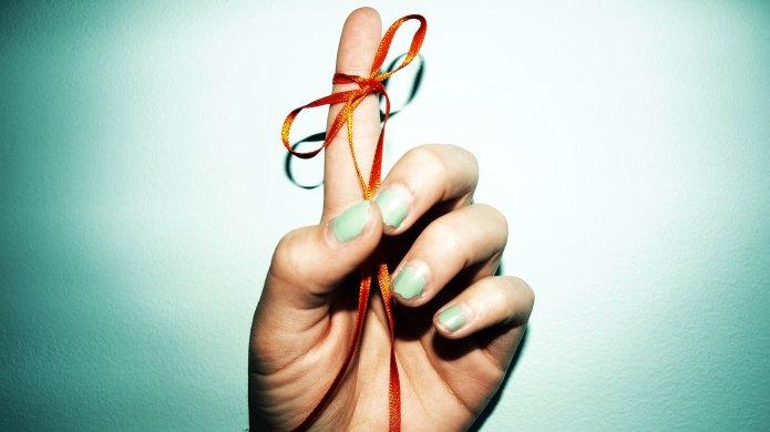 String tied around white person's finger