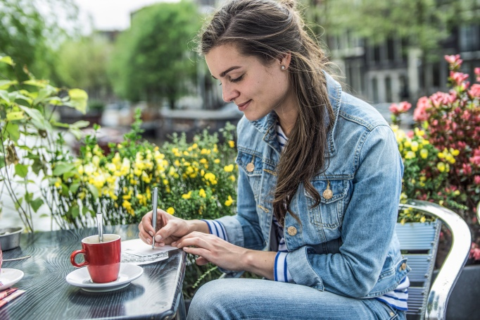 Woman writing a letter at an outdoor café