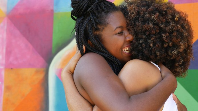Two Black women hugging on a