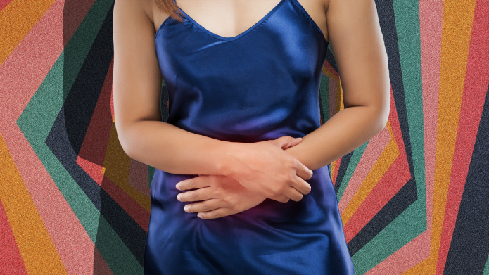 Woman clutches abdomen in pain.