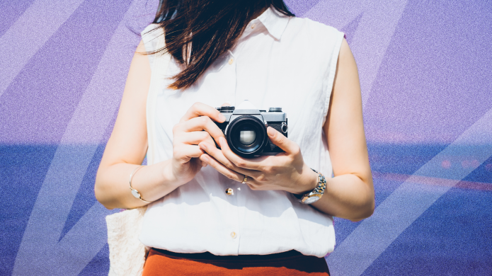 Brunette woman holds camera ready