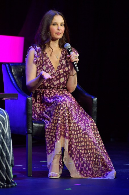 Ashley Judd sitting in a chair holding a microphone