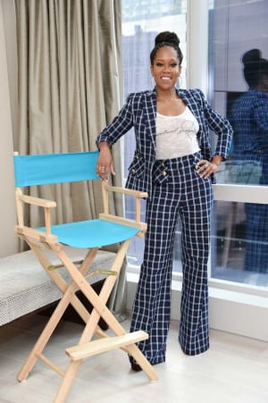Photo of Regina King standing next to a director's chair for the Her Shot Campaign with Gillette Venus