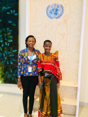Two women from Uganda in front of UN sign
