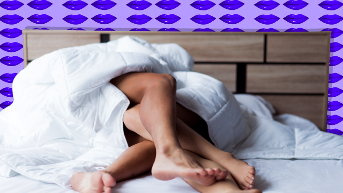 Couple in bed with legs intertwined.