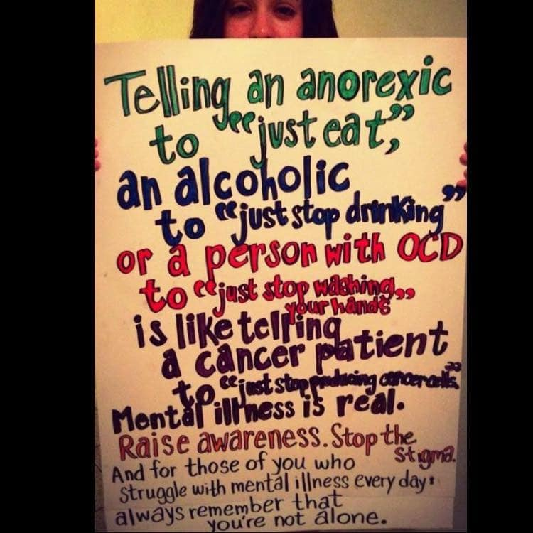 Woman holding sign about mental health stigma.