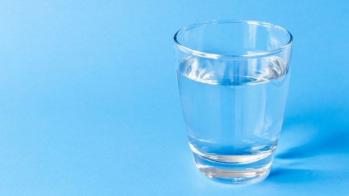Glass of water on blue background.