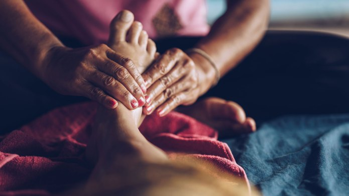 Woman getting reflexology on her foot