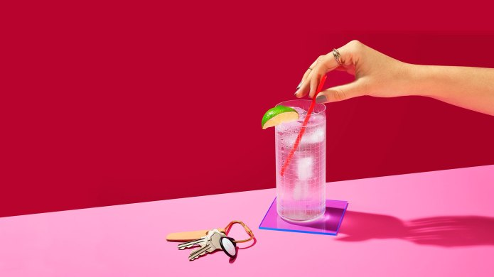 Woman's hand holding a cocktail straw