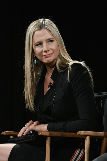 Mira Sorvino sitting in a chair