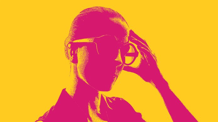 Woman holding her head wearing glasses.