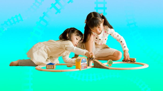 Two girls playing with toy train