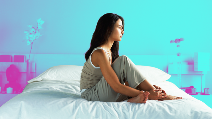 Profile of woman sitting on bed