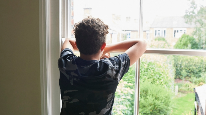 teen boy looking out window