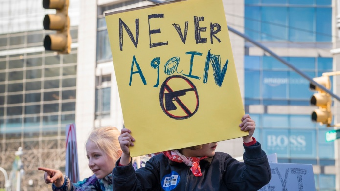 "Protester holds up a ""never again"""