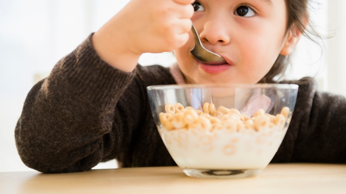 photo of girl eating bowl of